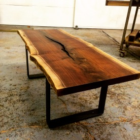 Walnut coffee table with steel base by Industrial Strength Design.